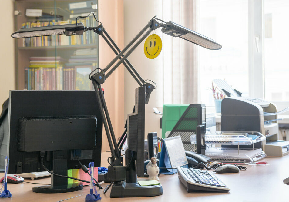 Workplace with table lamps. Work table in small office with window and bookcase.